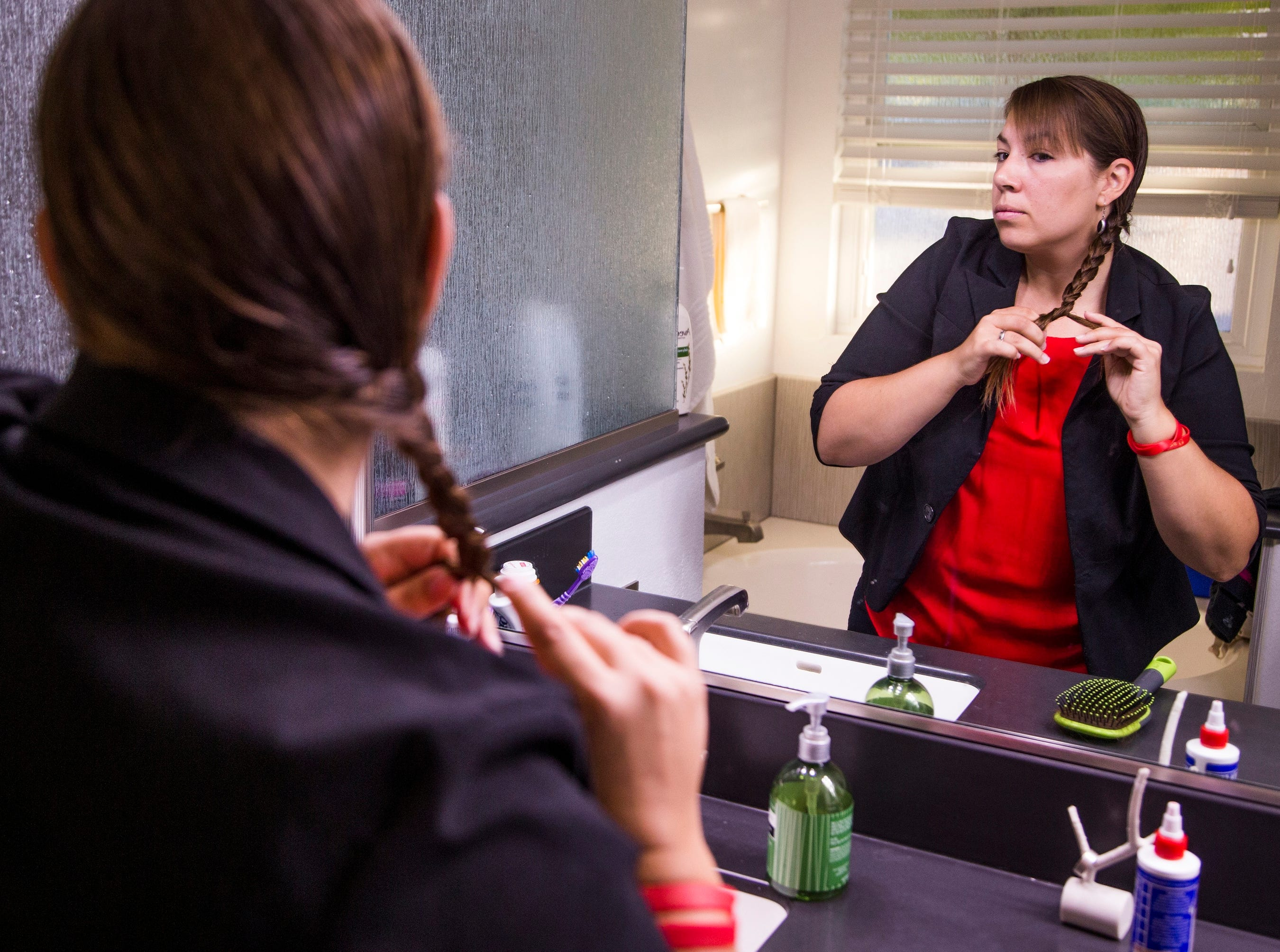Phoenix, AZ – Rebecca Garelli brushes her hair at 6:41 am before heading out for her 30-mile commute to Sevilla West Elementary School in Phoenix, Arizona, Monday, September 17, 2018. Garelli has been one of the leaders of the Red for Ed movement, demanding increased funding for education in Arizona.