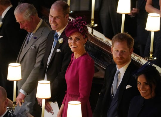 Prince William, Duchess Kate, Prince Harry and Duchess Meghan watch Princess Eugenie come down the aisle of St. George's Chapel.