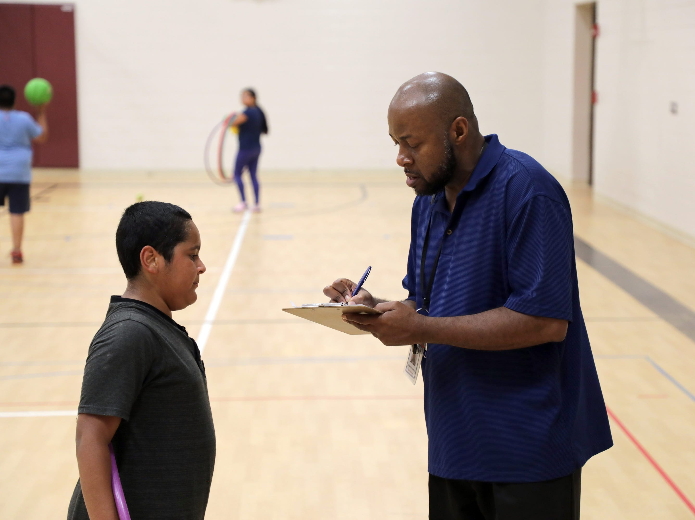 Racine WI – Edward Lawson checks in a student at the after school activities at Julian Thomas Elementary School.