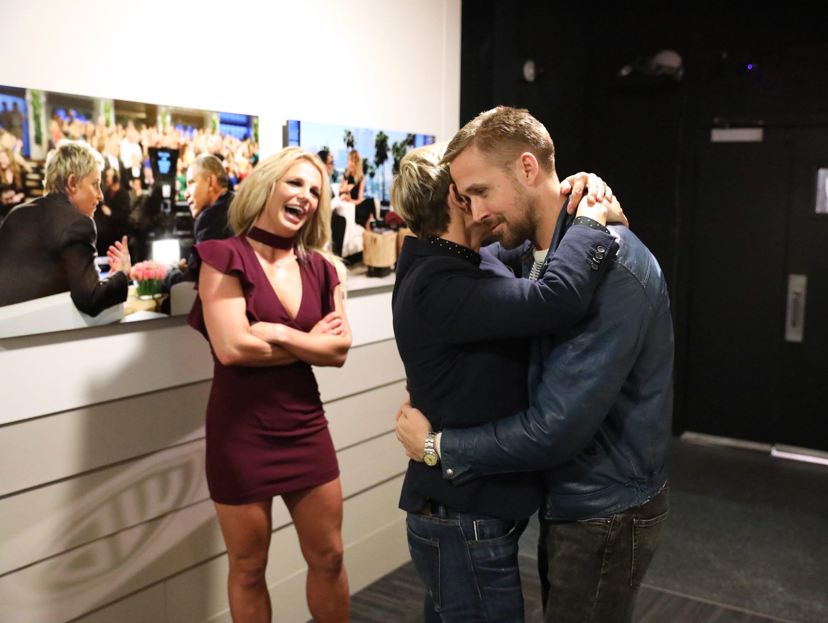 """Ellen DeGeneres gives Ryan Gosling a hug (as Britney Spears looks on) before """"The Ellen DeGeneres Show."""""""