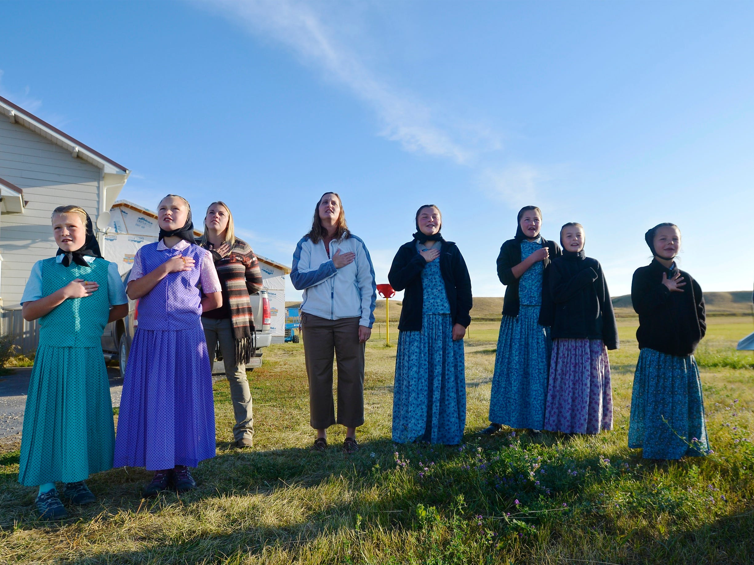Deerfield, MT – Traci Manseau, fourth from left, recites the Pledge of Allegiance with her students at the start of the day. Manseau is a teaching veteran of 23 years and she has spent her entire career teaching in one room rural school houses. She is currently teaching 15 students across seven different grade levels at the Deerfield Hutterite Colony in North Central Montana's Fergus County.