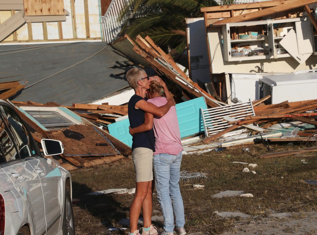 Becky Daniel hugs her wife, Monica Barber as they see the remains of their Beacon Hill home on Thursday. It was destroyed in Hurricane Michael.
