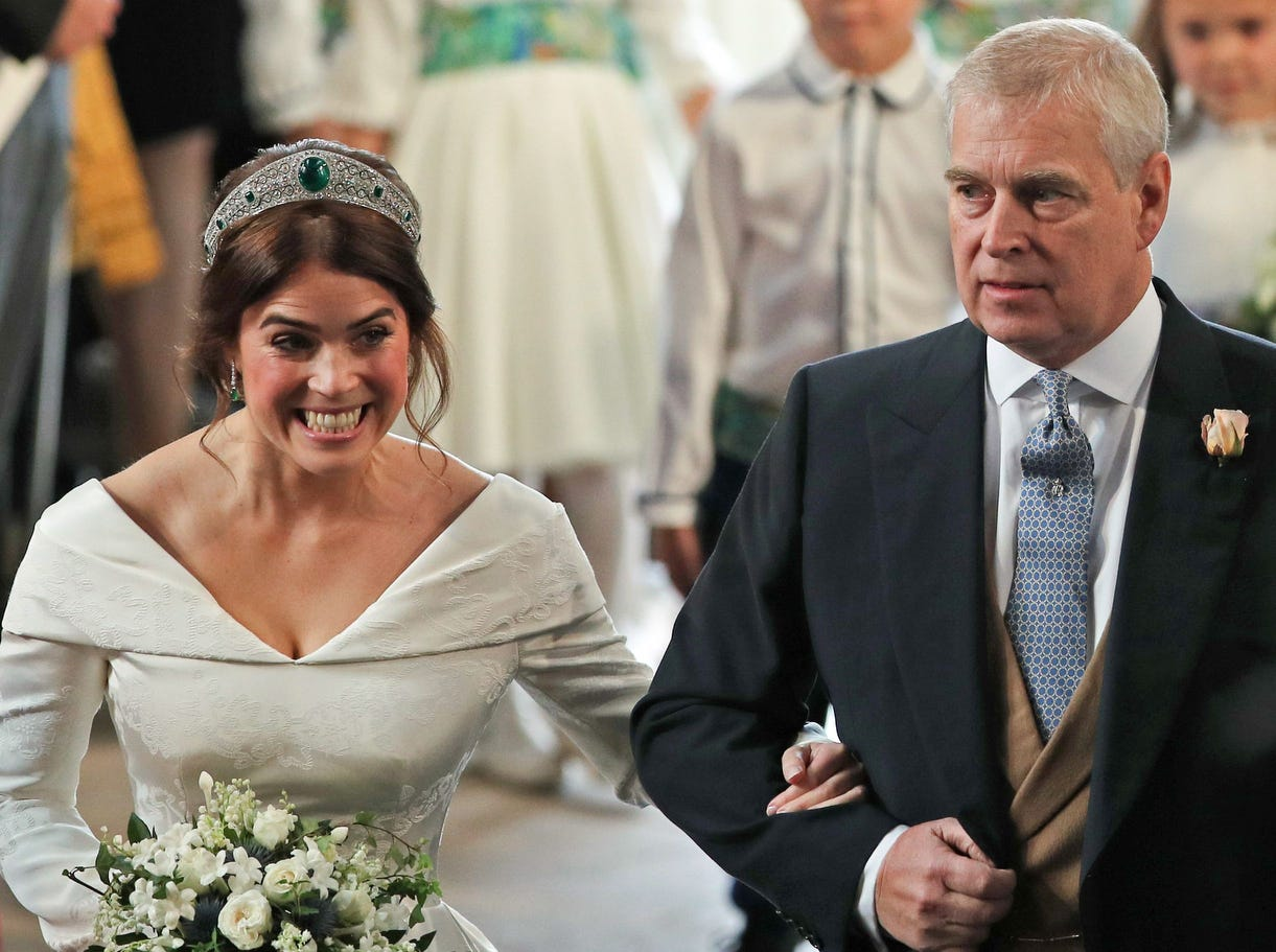 Britain's Princess Eugenie of York is allsmiles a she walks up the aisle with her father Britain's Prince Andrew, Duke of York,  to marry Jack Brooksbank during their wedding ceremony in St George's Chapel, Windsor Castle, in Windsor, on Oct. 12, 2018.