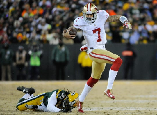 San Francisco 49ers quarterback Colin Kaepernick runs past Green Bay Packers cornerback Davon House during their 2013 NFC wild card playoff football game at Lambeau Field.
