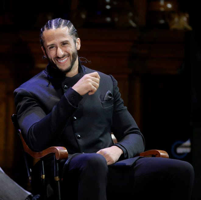 Colin Kaepernick is seated on stage during W.E.B. Du Bois Medal ceremonies at Harvard University.