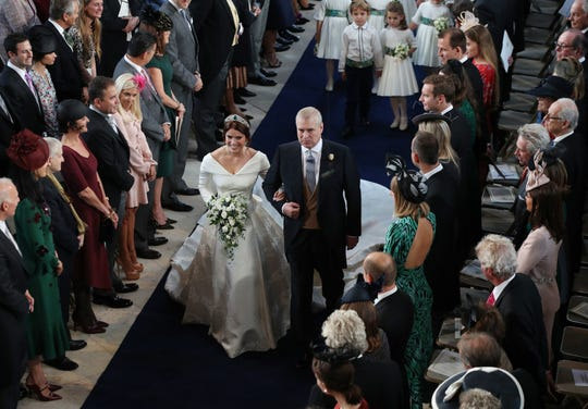Princess Eugenie of York accompanied by her father, Prince Andrew, Duke of York, walks up the aisle during her wedding ceremony to Jack Brooksbank at St George's Chapel, Windsor Castle, in Windsor, on Oct. 12, 2018.