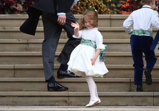 Princess Charlotte, who served as a bridesmaid, recovers from a wind-induced stumble on the church steps.