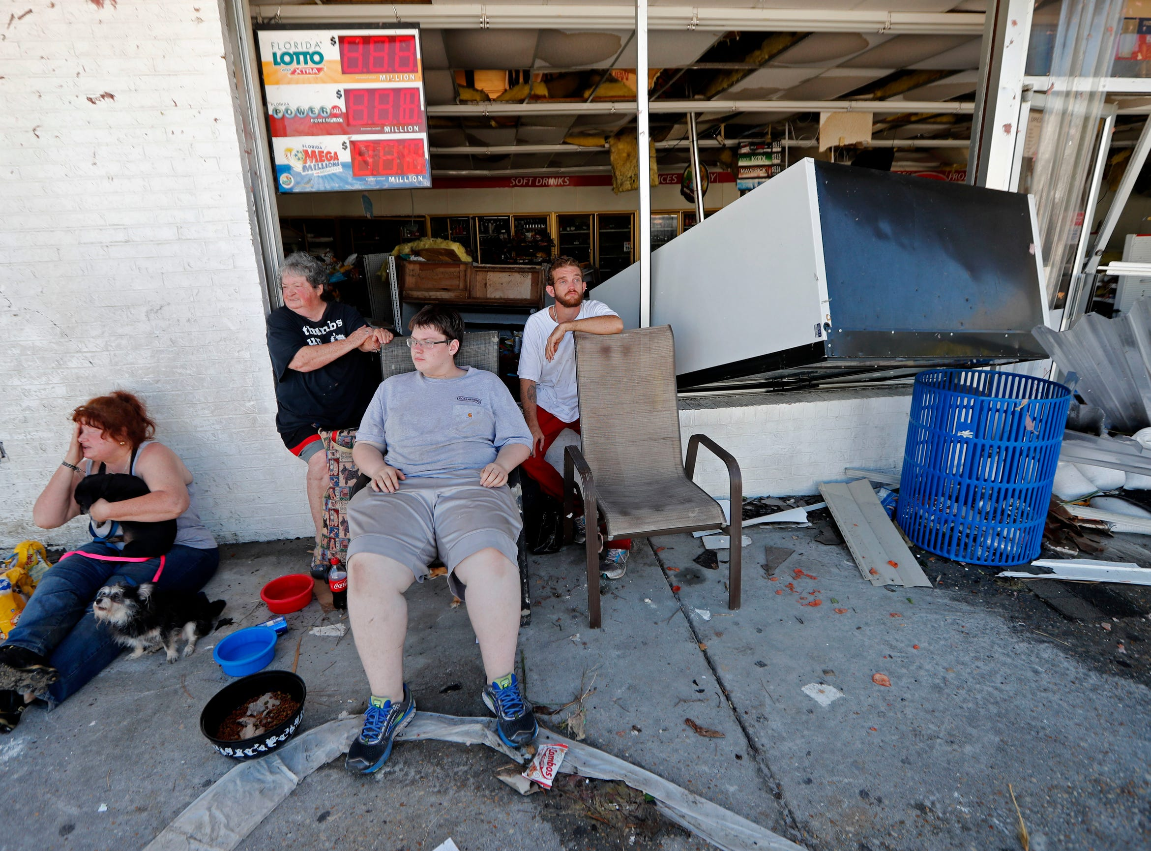 Dawn Vickers, left, her mother Patsy Vickers, son Ryder Vickers, and friend Robert Brock, right, who rode out Hurricane Michael in their now-destroyed home, sit in front of a damaged convenience store with nowhere to go, in Michael's aftermath, in Mexico Beach, Fla., on Oct. 11, 2018. Their house floated away from its foundation in the storm and they escaped the water by wading through a window.