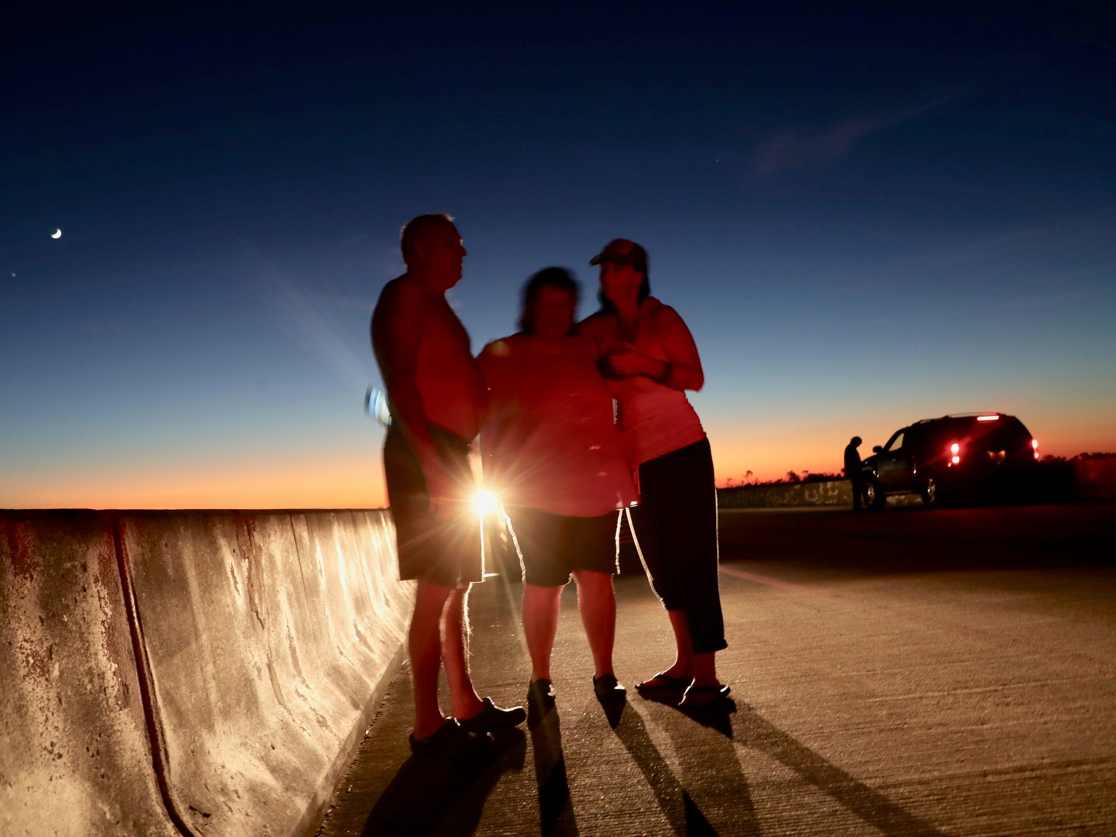 Rusty and Pam Burrows get comfort from Monica Fabie on top of the bridge  that  heads to Mexico City which was ground zero for Hurricane Michael, Oct. 11, 2018.