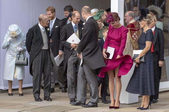 Duchess Kate laughed as she tried to hold down the skirt of her Alexander McQueen dress.