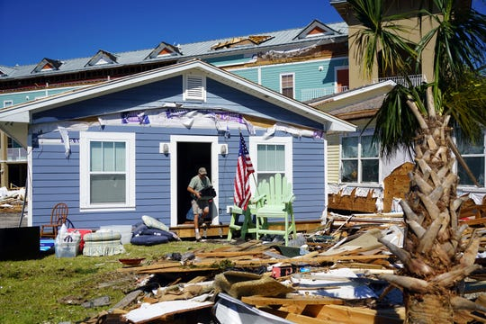 Kenny Faris helps his sister in law clear out her home in Mexico Beach, Florida, on Oct. 12, 2018, after Hurricane Michael lifted the building off its foundation and floated it about 100 yards into a parking lot. The home's deck remains where it belongs.