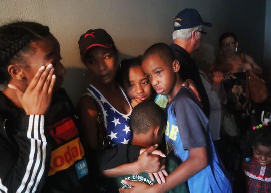 Shekinah Waddell hugs and prays with her children Trinity, Christian and Caris Devore as Hurricane Michael passes Panama City, Fla.