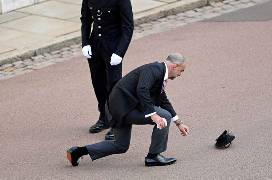 A guest loses a hat in the wind as he arrives for the wedding of Princess Eugenie of York and Jack Brooksbank at St George's Chapel, Windsor Castle, Oct. 12, 2018.
