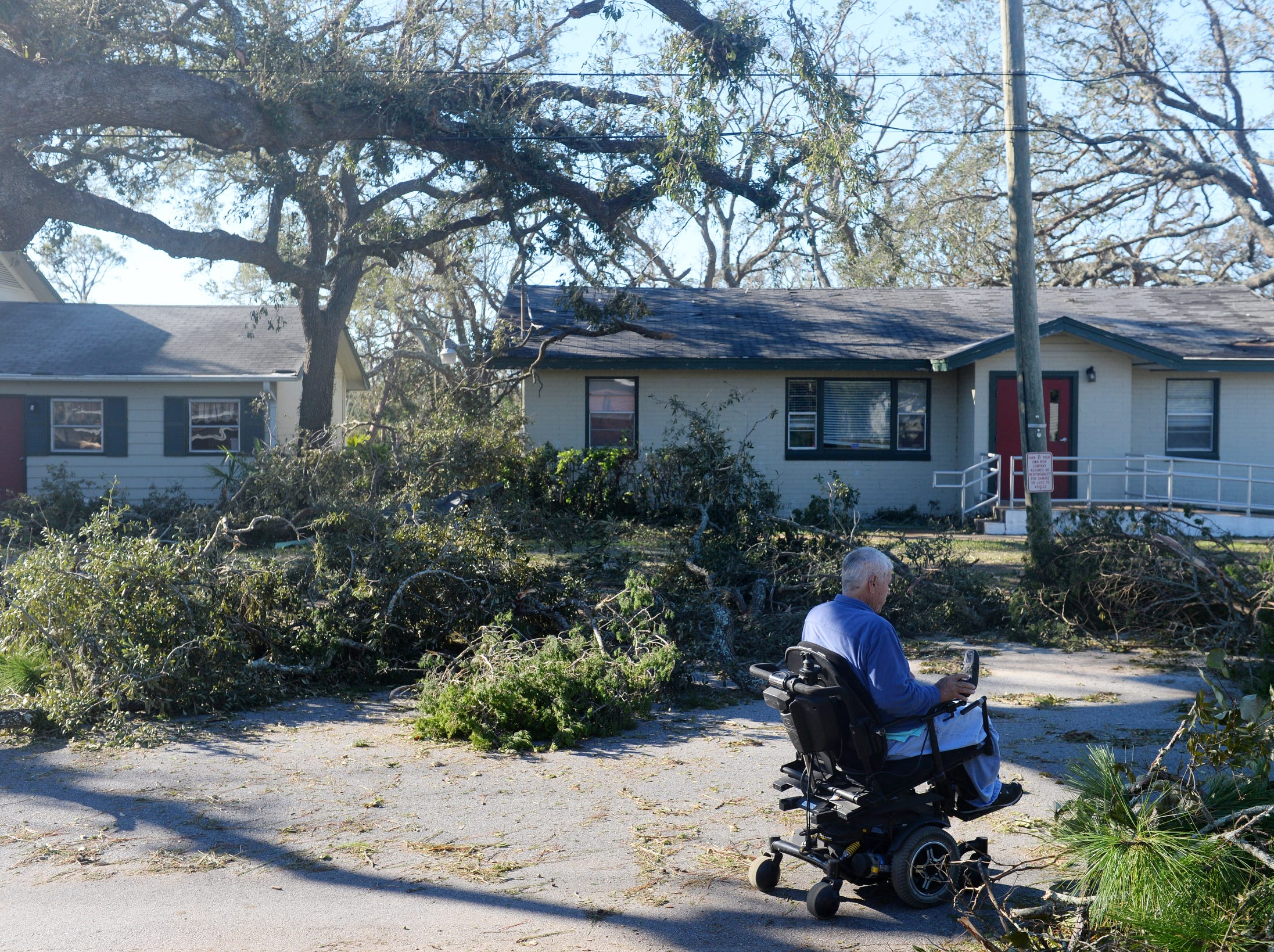 "Leroy Retherford makes his way down his driveway in Panama City, Fla., on Friday,  after family members helped to clear debris left by Hurricane Michael. ""By the time they said it was going to come in as a Category 4, it was too late to leave,"" Retherford said."