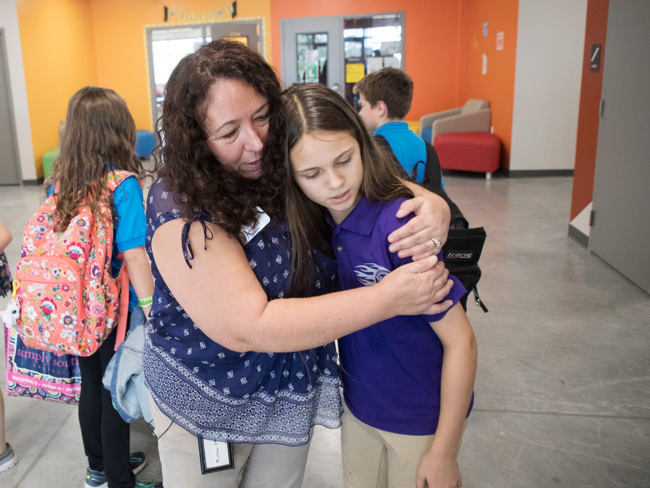 Babcock Ranch, FL – Lori McLain embraces student, Grace Hilliker,12, at the end of classes. Hilliker gave McLain an appreciative note.