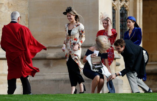 A guest bends down to catch her hat that was lost in the wind when she arrives to attend the wedding of Princess Eugenia of York and Jack Brooksbank in the Chapel of St. George, Windsor Castle, on October 12, 2018.