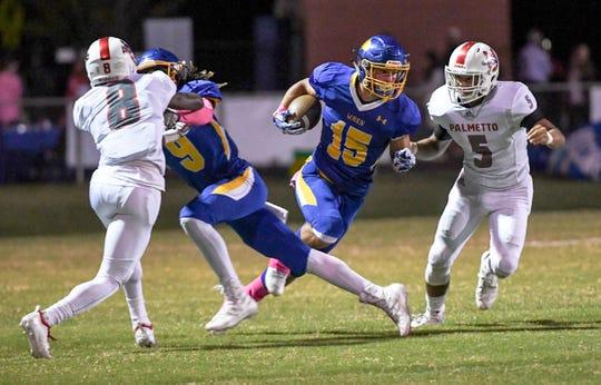 Wren junior Tyler Cherry (15) runs by Palmetto junior Landon Owens during the first quarter at Wren High School in Piedmont on Friday, October 12, 2018.
