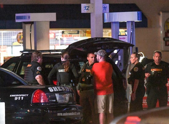Anderson County Sheriff Deputies and SWAT team members stand around a black Chevrolet car in the parking lot of the Stop-A-Minit on S.C.24 and S.C.28 Bypass in Anderson on Friday, October 12, 2018.