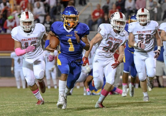 Wren senior quarterback Tyrell Jackson (1) runs by Palmetto Chase Froedge during the first quarter at Wren High School in Piedmont on Friday, October 12, 2018.