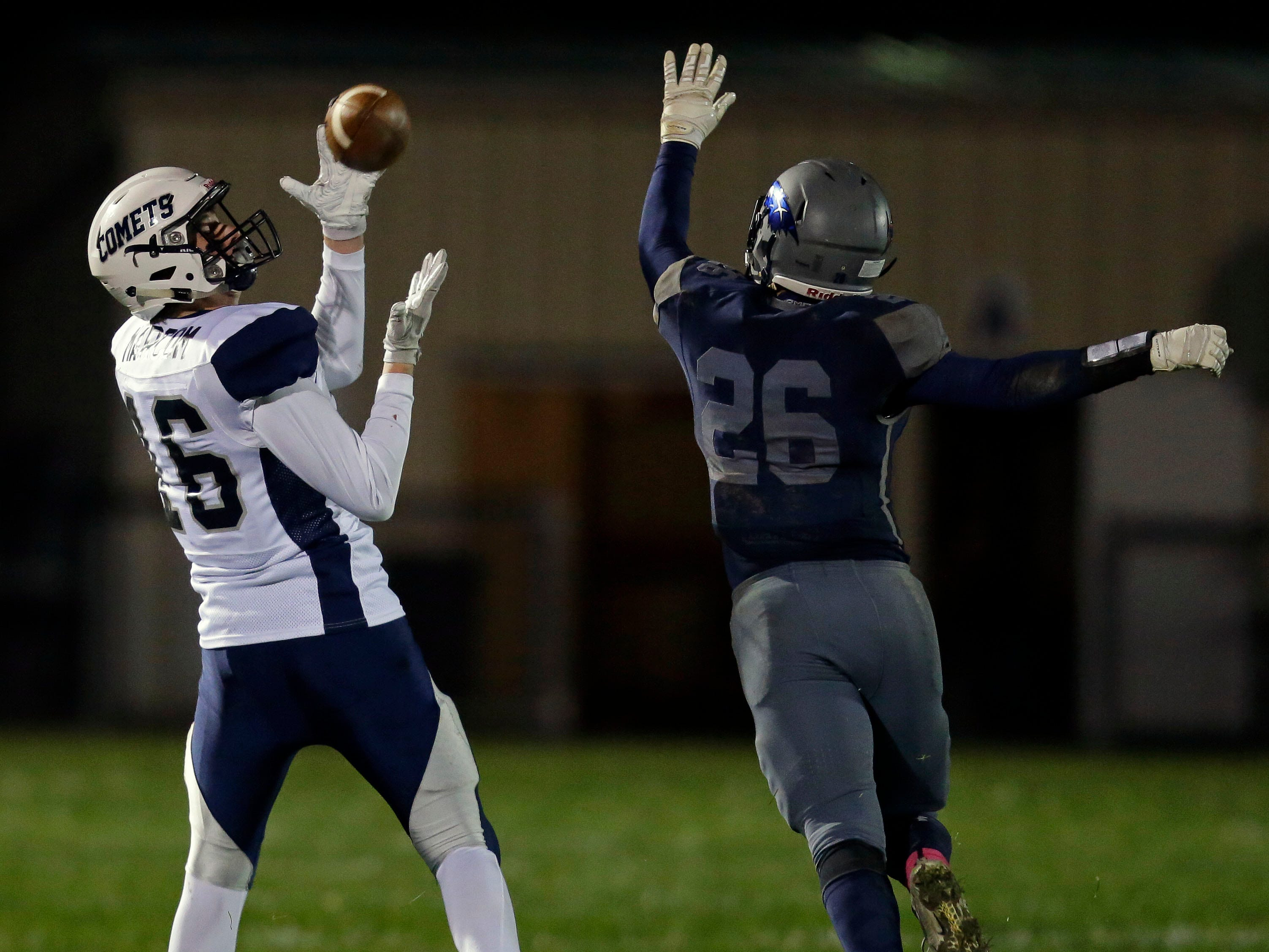 Hunter Marcom of Waupaca hauls in a pass while being defended by Chris VandenHeuvel of Xavier in a Bay Conference football game Friday, October 12, 2018, at Rocky Bleier Field in Appleton, Wis.