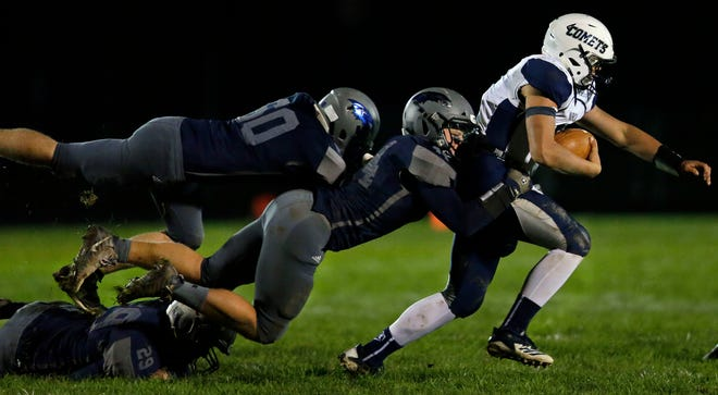 Davis Levine of Waupaca is tackled by Mac Strand and Jacob Janke (rear) of Xavier in a Bay Conference football game Friday at Rocky Bleier Field in Appleton.