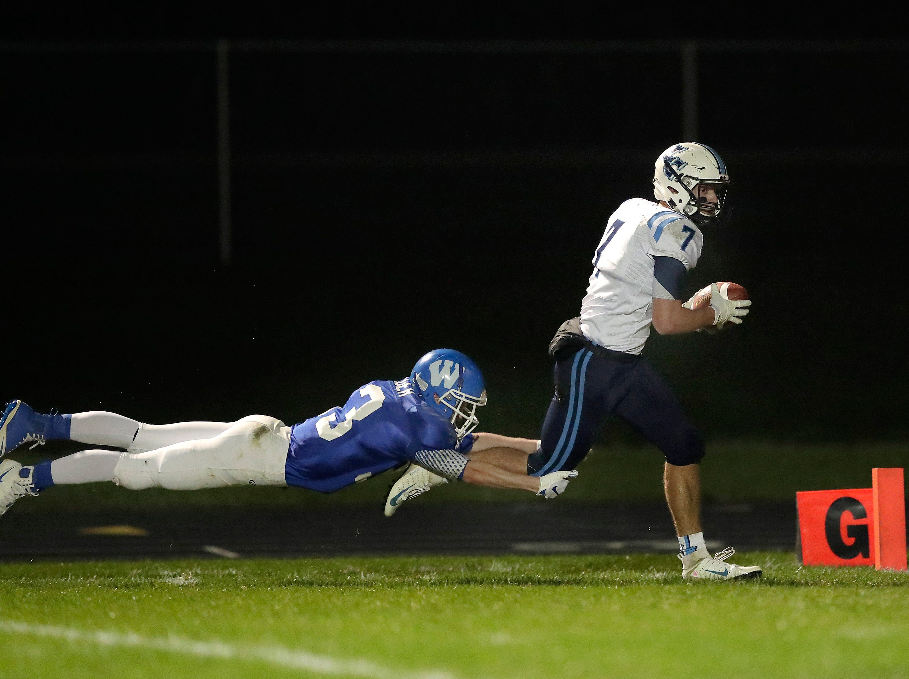 Little Chute High School's #7 Adam Hietpas scores against the defense of Wrightstown High School's #33 Will Braeger during their North Eastern Conference football game on Friday, October 12, 2018 in Wrightstown Wis. 