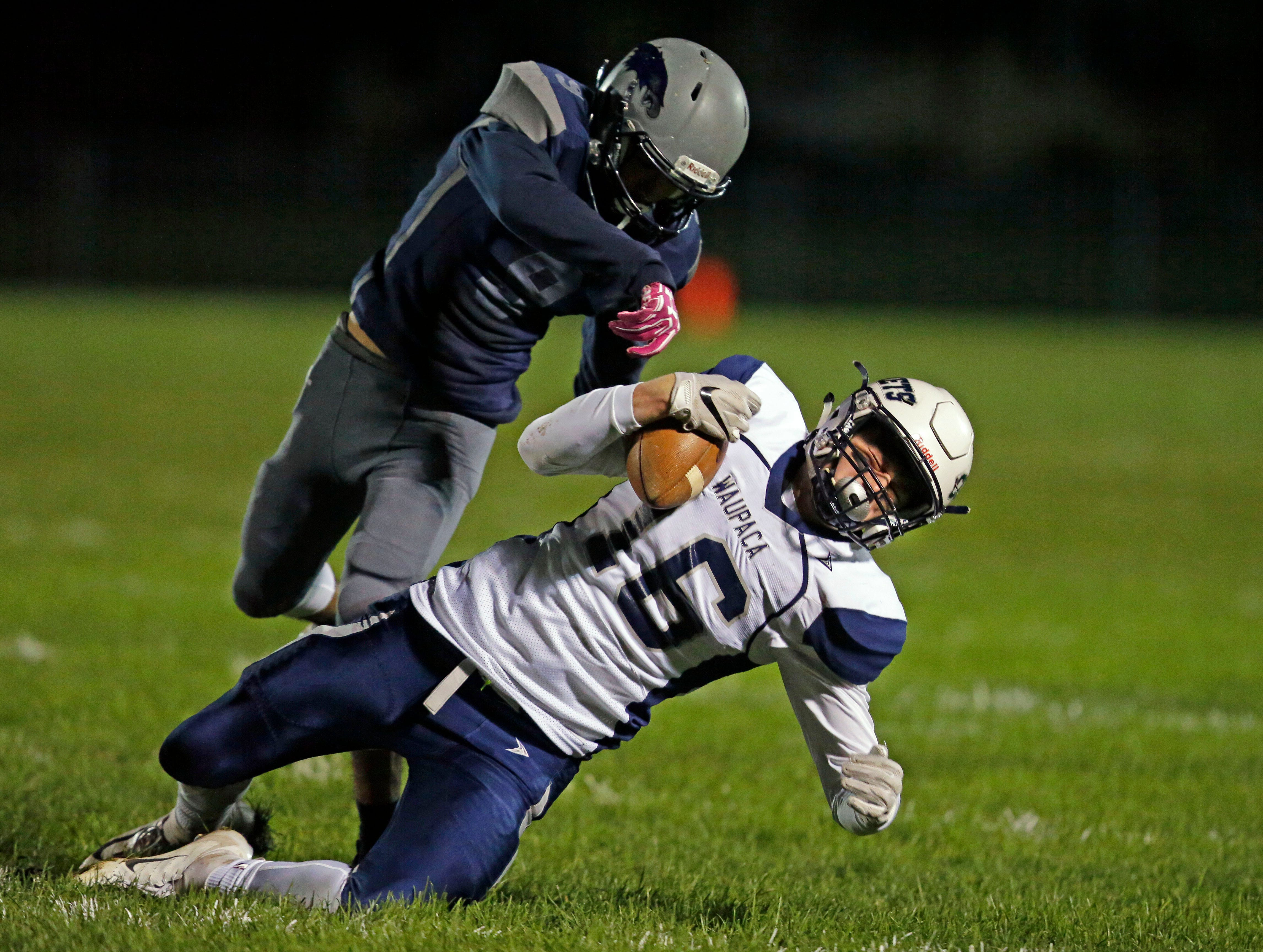 Hunter Marcom of Waupaca is brought down by Frankie Rasmus of Xavier in a Bay Conference football game Friday, October 12, 2018, at Rocky Bleier Field in Appleton, Wis.