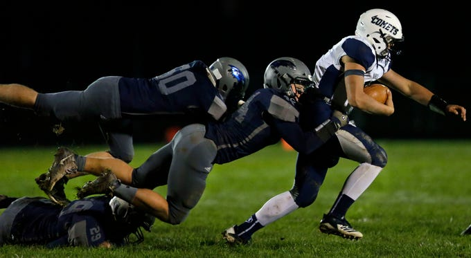 Davis Levine of Waupaca is tackled by Mac Strand and Jacob Janke (rear) of Xavier in a Bay Conference football game Friday, October 12, 2018, at Rocky Bleier Field in Appleton, Wis.