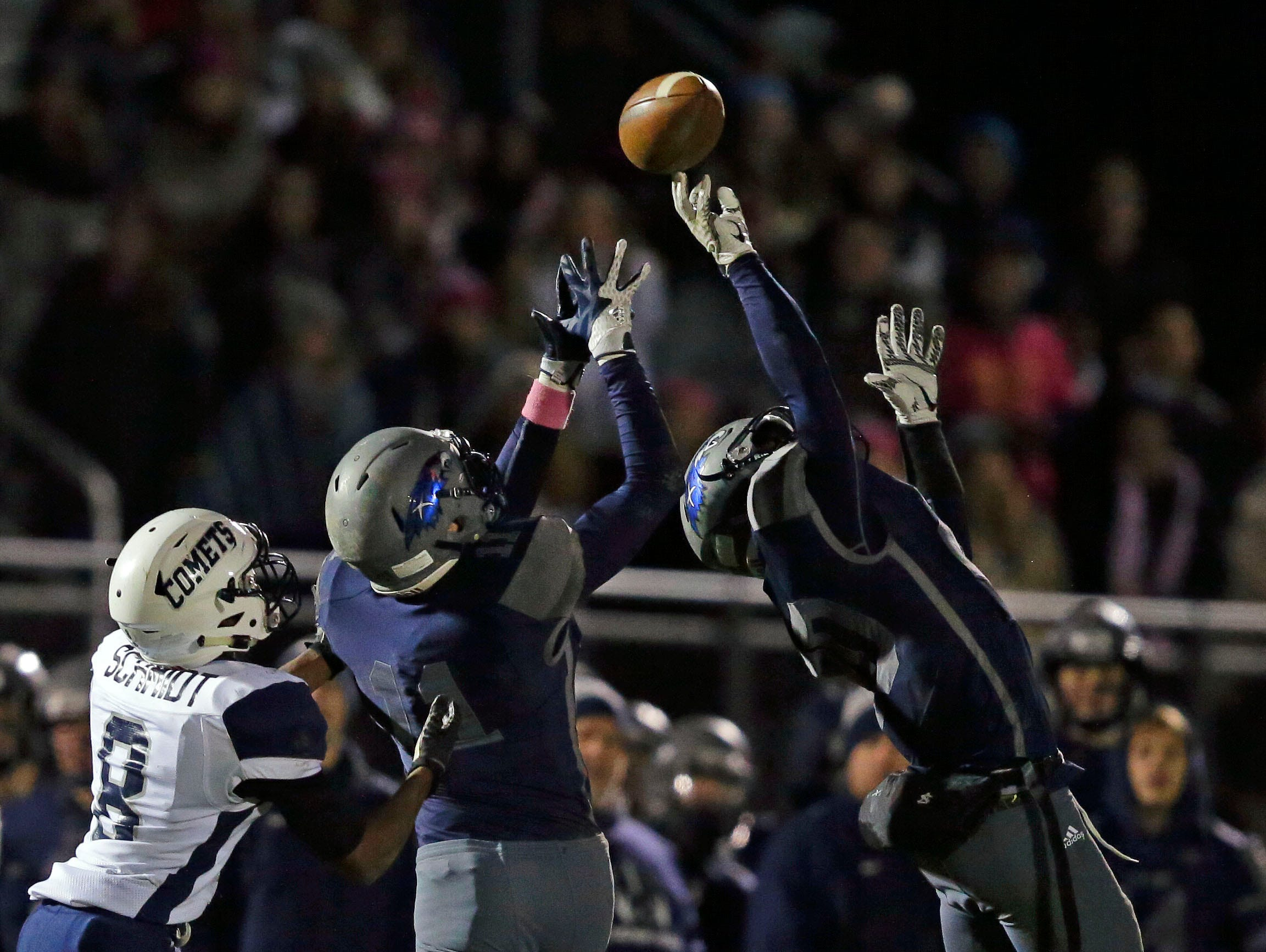 Tj Van Eperen and Alex Hahlbeck of Xavier almost intercept a pass for Terry Schmidt of Waupaca in a Bay Conference football game Friday, October 12, 2018, at Rocky Bleier Field in Appleton, Wis.