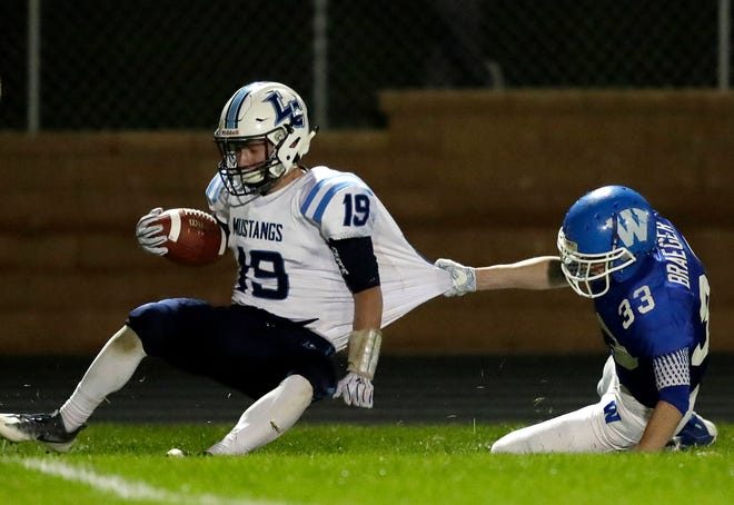 Little Chute's Jacob Lillge is dragged down by Will Braeger of Wrightstown during Friday's game.