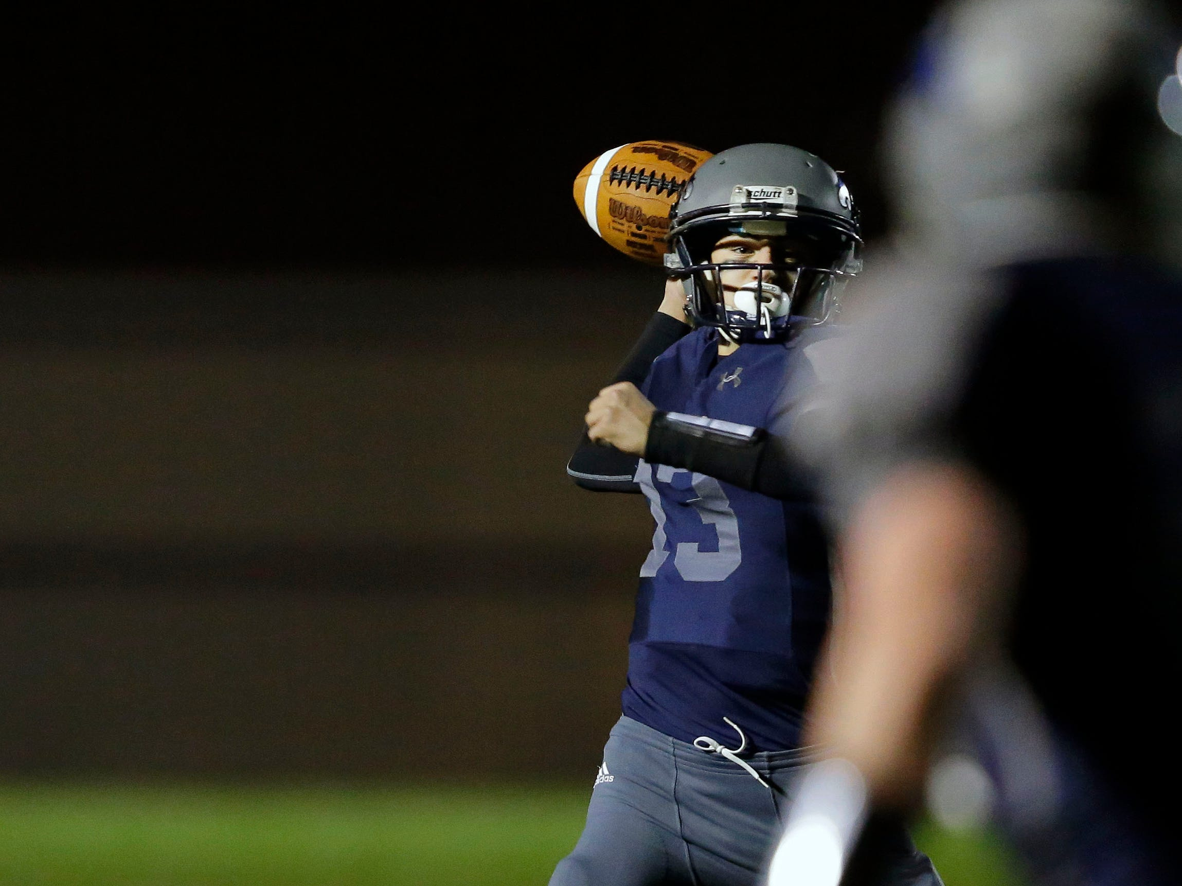 Ray Zuleger of Xavier looks for a receiver as the Hawks take on Waupaca in a Bay Conference football game Friday, October 12, 2018, at Rocky Bleier Field in Appleton, Wis.
