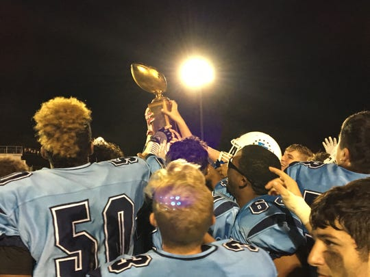 Freehold Township's players celebrate with the Duke Trophy.