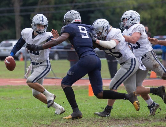 Manasquan quaterbak Ryank O'Leary tries to outrun outstretched arms of Mater Dei's Shittah Sillah but gets sacked during first quarter action. Manasquan Football vs Mater Dei in Middletown, NJ on October 13, 2018.