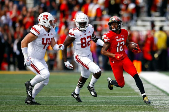 Maryland punt returner Taivon Jacobs, right, rushes past Rutgers defenders Max Anthony, left, and Zihir Lacewell in the first half of an NCAA college football game, Saturday, Oct. 13, 2018, in College Park, Md. (AP Photo/Patrick Semansky)