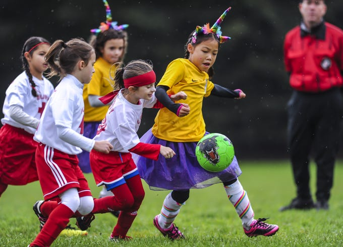 Mandi Guo of the Freehold Thunder, right, tangles with Howell Surf defenders at Michael J. Tighe Park in Freehold on Oct. 13, 2018. Freehold Soccer League hosted their 20th Halloween-themed Fright Fest Tournament where teams wear Halloween costumes as uniforms and the fields are decked out with spooky decorations.
