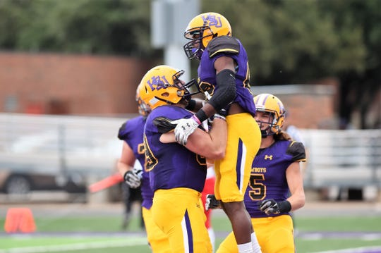 Hardin-Simmons tight end Woody Watson (89) lifts receiver Kevi Evans (82) following a touchdown against Sul Ross State. Evans and Rae Millsap have become weapons for the Cowboys on special teams and now in the team's offense.