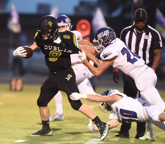 Dublin running back Hagen Huffman powers past two Tolar defenders during a run in the first quarter at Memorial Stadium on Oct. 12. The Lions won 28-27.