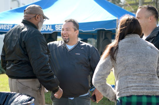 Republican candidate for Sheriff of Buncombe County Shad Higgins talks with Reggie Ray, right, during a Cops for Kids Bike Run event in Weaverville on Oct. 13, 2018.