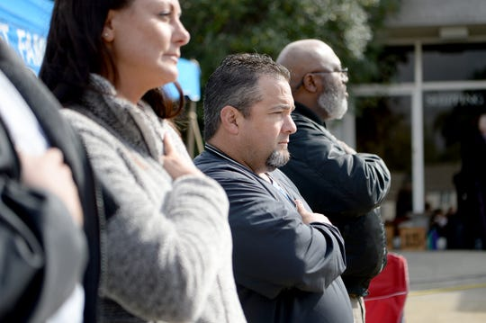 Republican candidate for Sheriff of Buncombe County Shad Higgins observes the flag during the singing of the National Anthem at a Cops for Kids Bike Run event in Weaverville on Oct. 13, 2018.