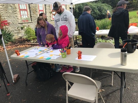 Kimberly and Jared Bosket look at ideas for the park's entryway project with their daughters Ellie age 7 and Emma age 5.