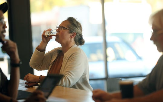 Cathy Tomko, of Bremerton, tests one of the many custom brews at Crane's Castle Brewing on Riddell in East Bremerton.