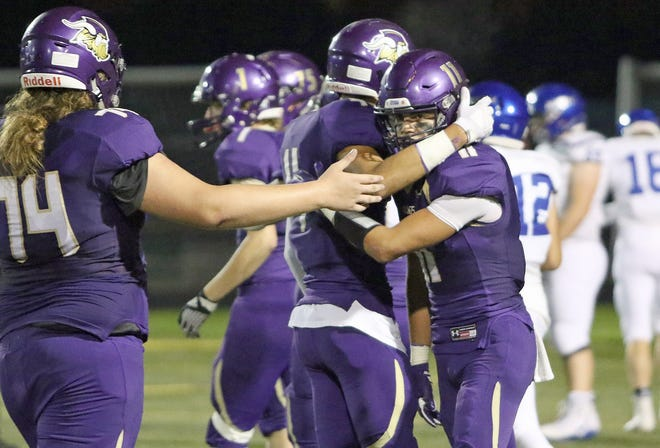 North Kitsap's John Jones (right) gets hugged by teammates during the Vikings' 53-6 win over North Mason on Friday in Poulsbo.