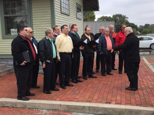 """The United in Harmony men's chorus sings """"The Star Spangled Banner"""" at the dedication of the restored depot."""