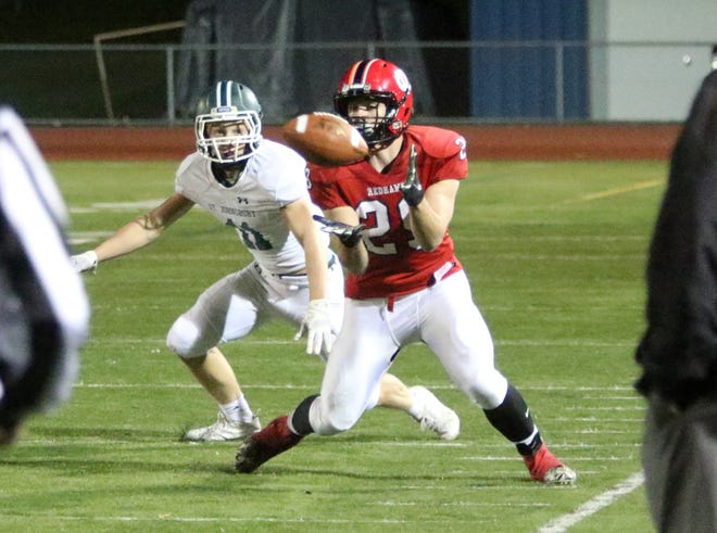 CVU senior Alex Murray hauls in a pass in front of a St Johnsbury defender during the Redhawks loss on Friday night.