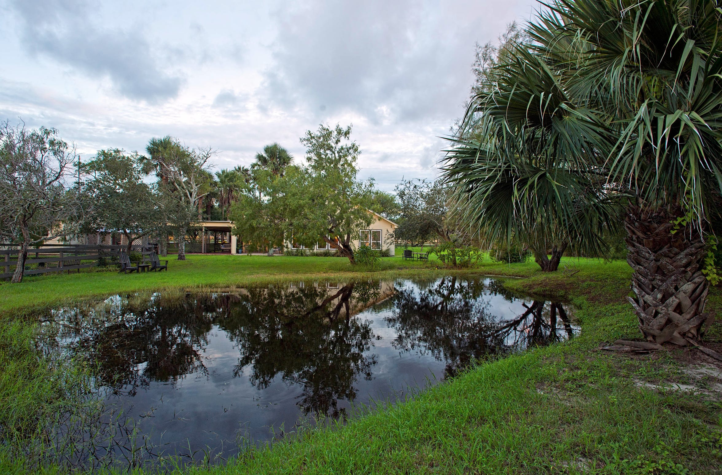 The home is reflected in the pond which is surrounded by trees and is the spot for frequent wildlife sightings.