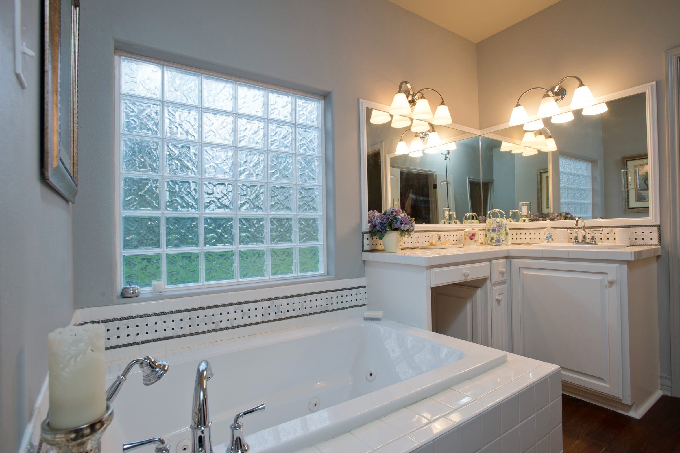 The master bath in the second living suite is fully equipped with a whirlpool garden tub with a glass brick window