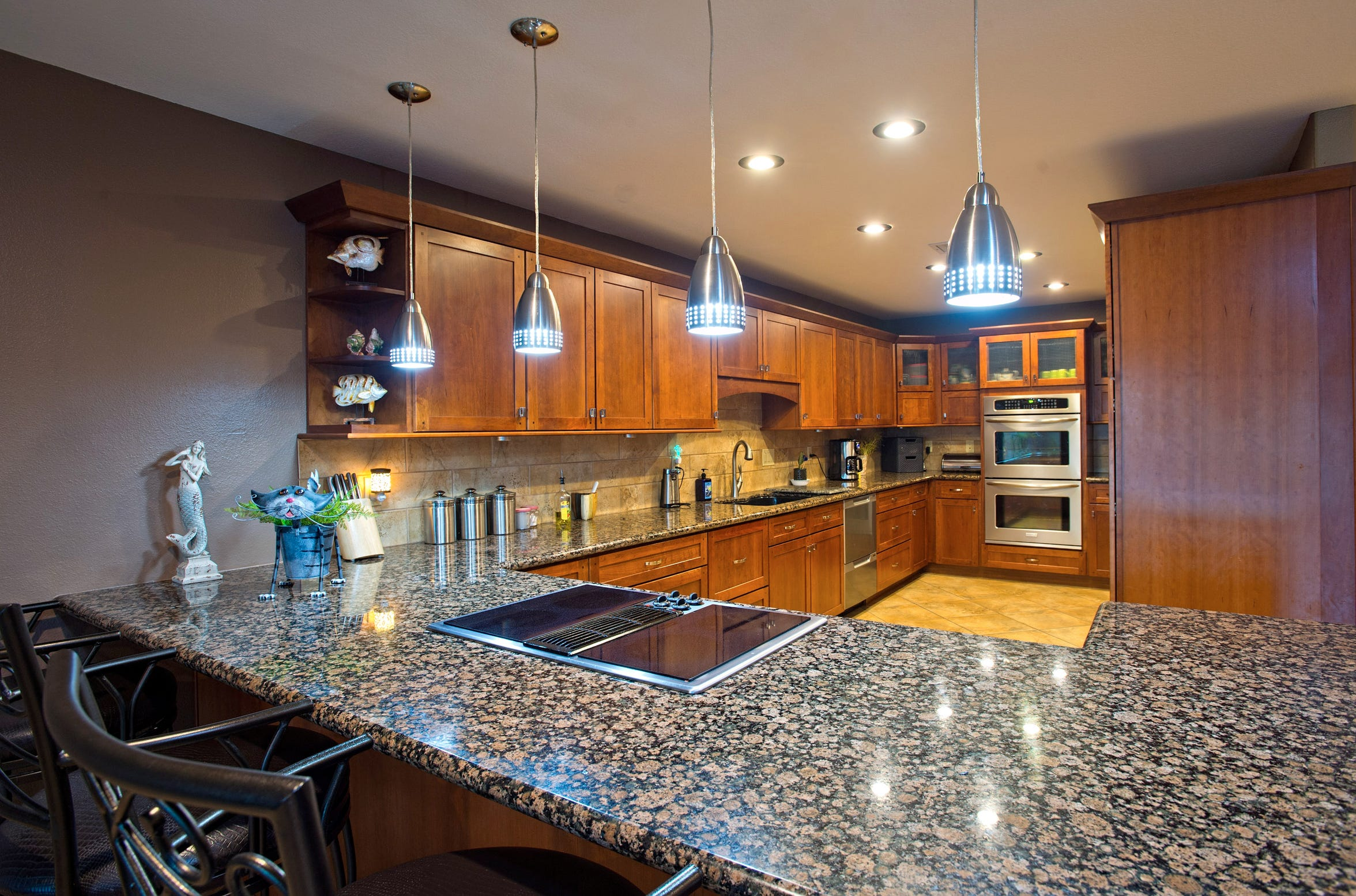 The kitchen features a double door dishwasher, custom cabinetry, pull out pantry, built in Frigidaire Extra wide fridge/freezer, granite counters and a breakfast bar