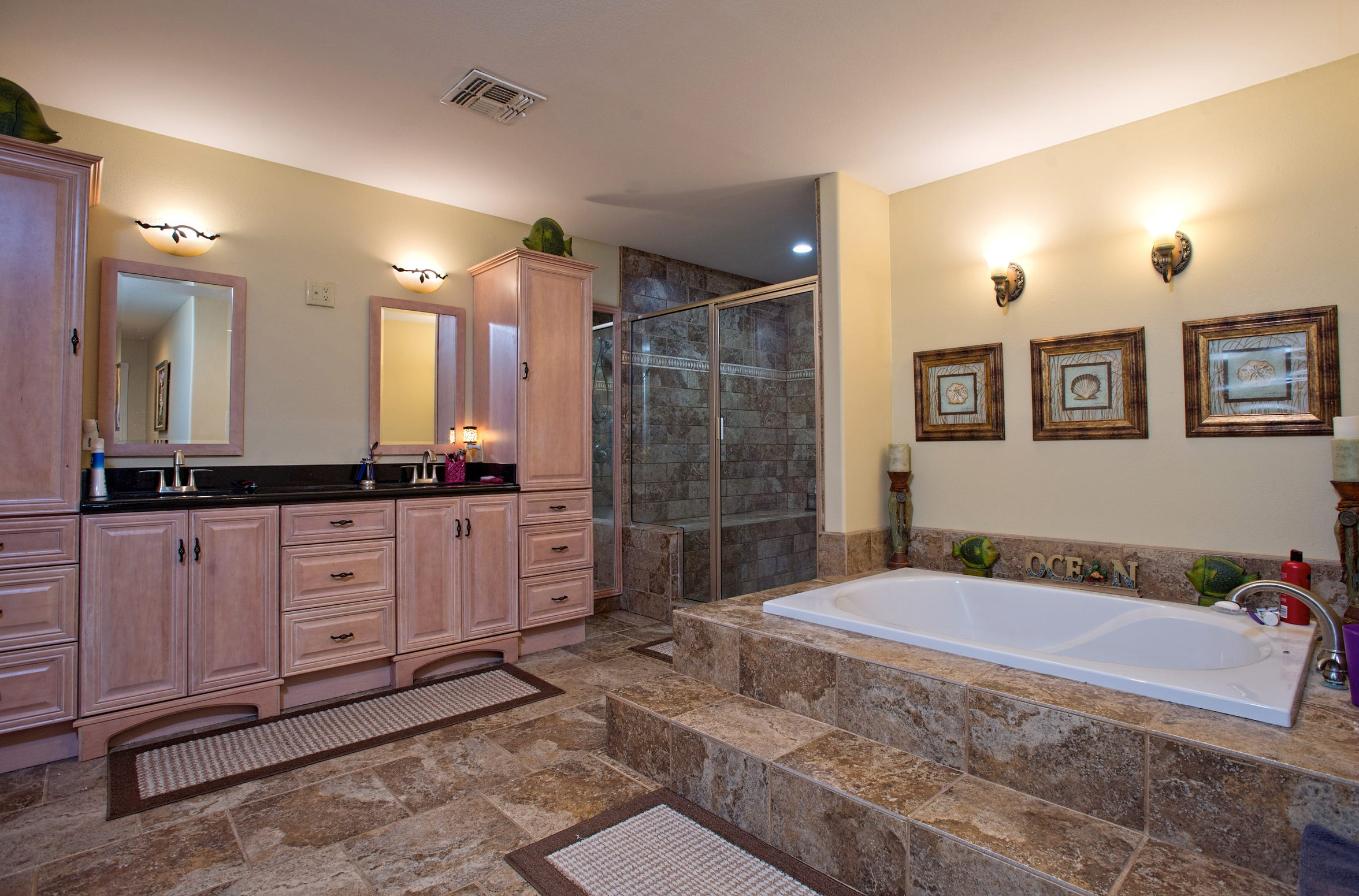 The luxurious and fully equipped tiled master bath features a walk in shower, soaking tub and generous cabinet space