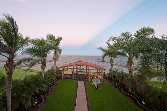 Spectacular views from the upper level balcony across the lushly landscaped yard of the outdoor living space, the pool and Baffin Bay.