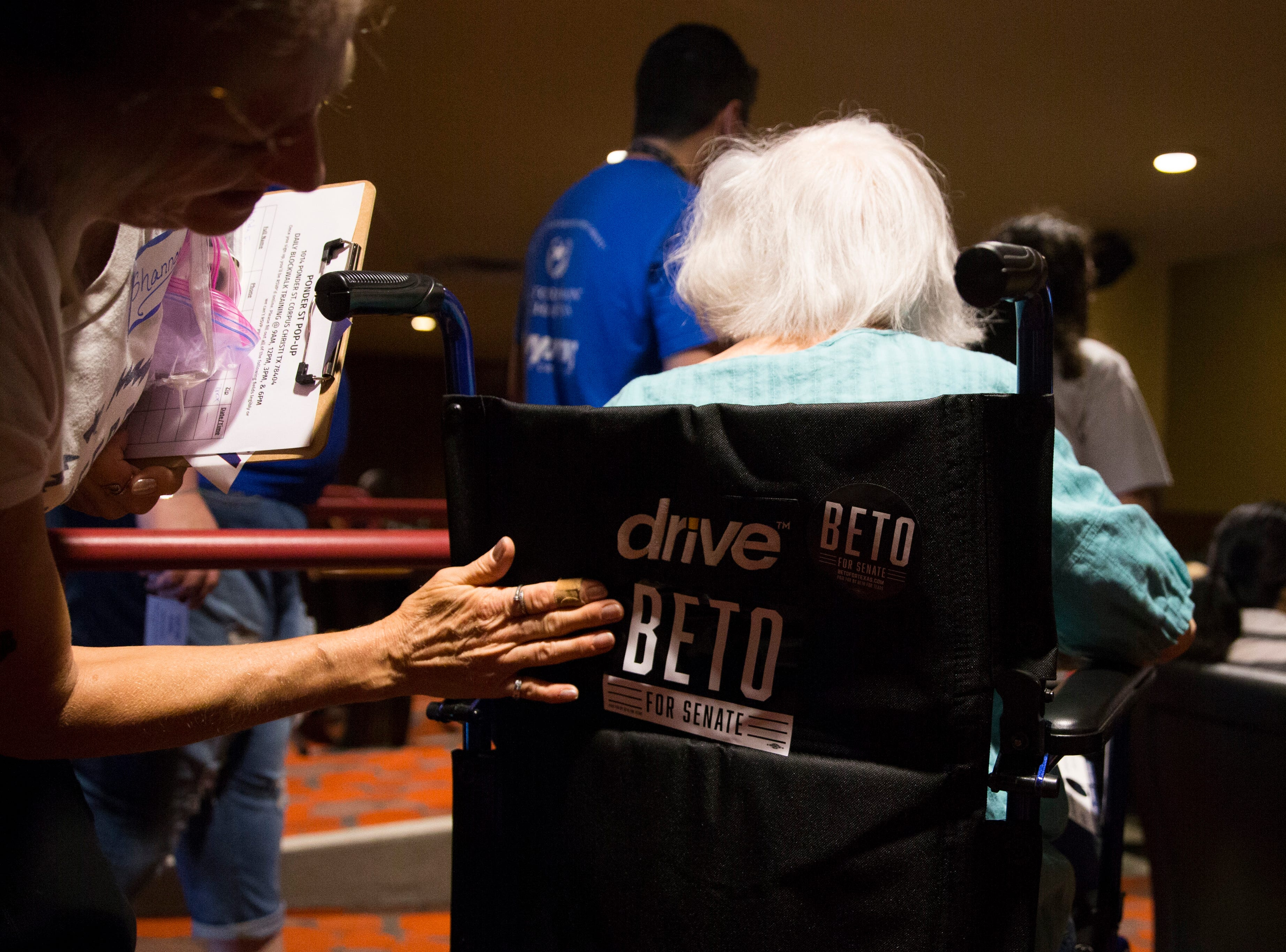 A woman attaches a Beto O'Rourke sticker to a wheel chair  during a campaign event on Saturday, Oct. 13, 2018 at Del Mar College in Corpus Christi.